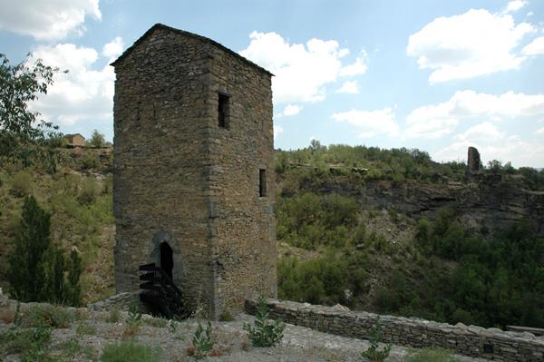 Torre cuadrada. Al fondo, torre cilíndrica